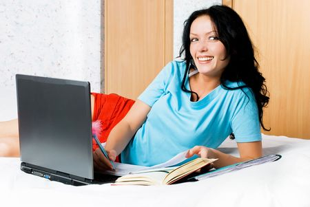 happy laughing brunette girl with a laptop doing homework photo