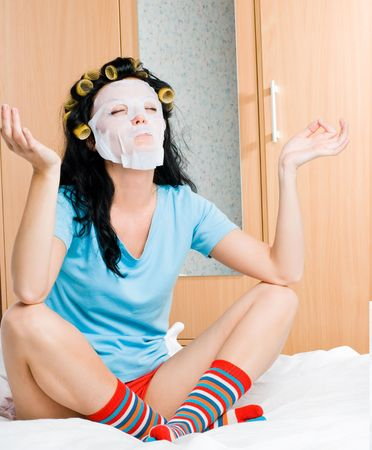 young woman wearing hair curlers and a mask sitting on the bed at home photo
