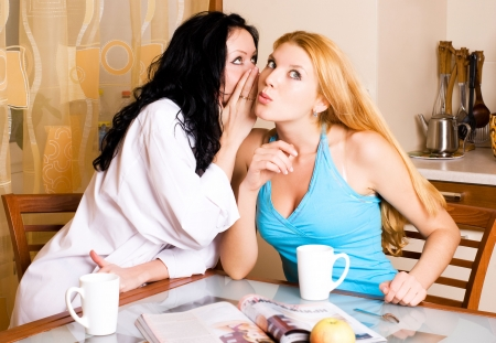 two young beautiful gossiping women at home in the kitchen Stock Photo