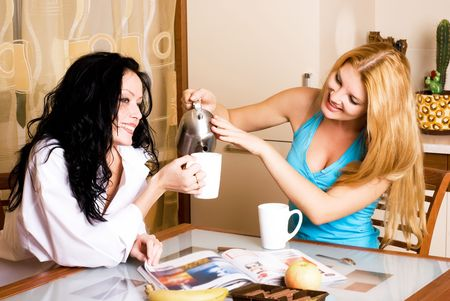 two young beautiful women drink tea in the kitchen and gossip photo