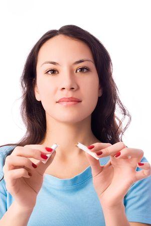 joven fumando: joven y bella mujer morena romper un cigarrillo aislado contra el fondo blanco