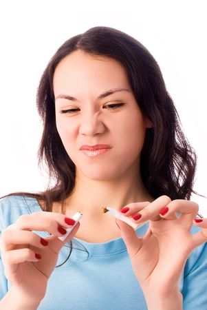 persuade: young brunette woman breaking a cigarette and frowning isolated against white background