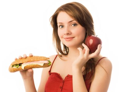 beautiful young woman choosing between an apple and hot dog photo