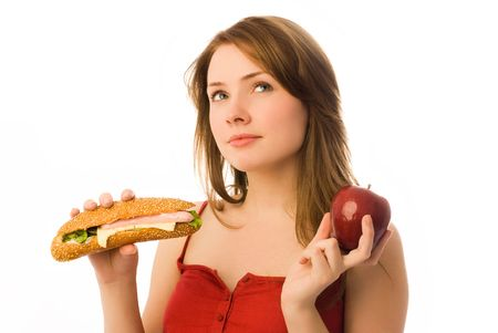 beautiful girl choosing between an apple and hot dog isolated against white background photo