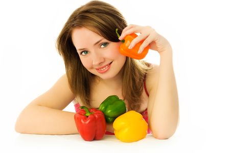 beautiful young brunette woman sitting by the table with colorful peppers  photo