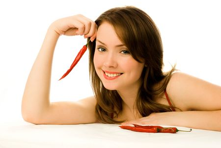 coquettish: sexy brunette woman with red chili peppers isolated against white background
