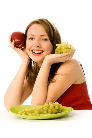 cheerful young woman with grapes and an apple isolated against white background photo