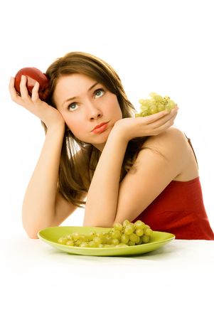 beautiful sad woman with an apple and grapes unwilling to eat fruit photo