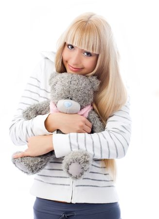 cute blond girl embracing her Teddy bear isolated against white background photo
