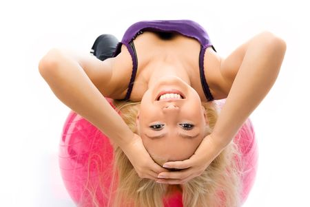 beautiful happy young woman with long blond hair works out on the fitness ball