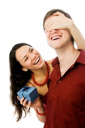 dar un regalo: alegre hermosa mujer morena le da un regalo a su marido