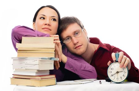 joyless: two lazy students sitting by the table with a lot of books and unwilling to do homework Stock Photo