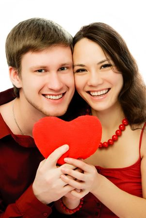 happy laughing couple with a heart-shaped pillow in their hands photo