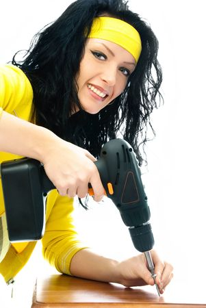 beautiful cheerful young brunette woman with a drill in her hands photo