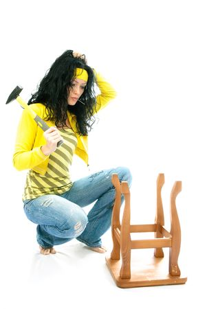 puzzled young brunette woman with a hammer repairs an old chair Stock Photo