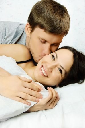 have: happy young man and woman wake up in the morning  in bed and kiss