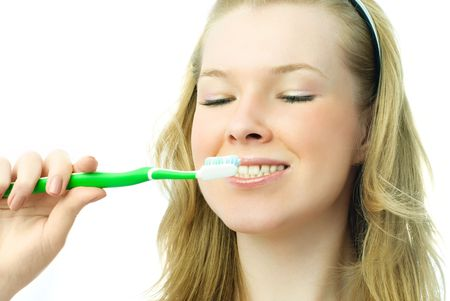 portrait of an attractive young blond woman brushing her teeth photo