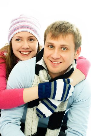 happy young man and woman dressed in warm winter clothes embrace and laugh photo