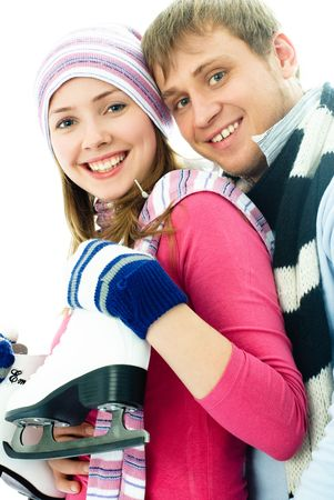 portrait of happy beautiful cheerful young couple going ice-skating photo