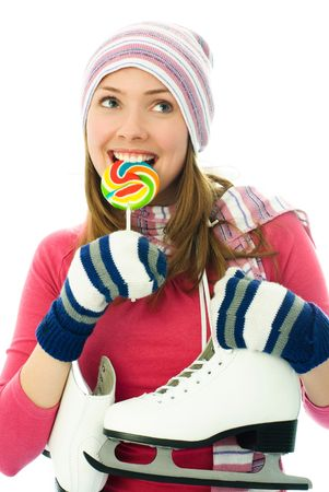 iceskating: beautiful young cheerful woman going ice-skating and eating a candy Stock Photo