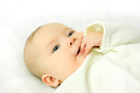 portrait of a cute four months old baby boy sucking his fingers and smiling photo