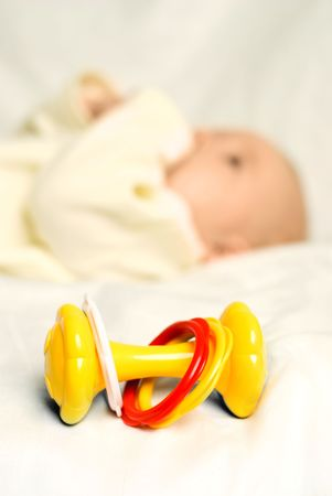 tiny baby lies on the bed with a colorful toy near him (focus on the toy) photo