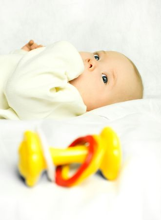 cute four months old baby boy on the bed with a colorful toy (focus on the baby) photo
