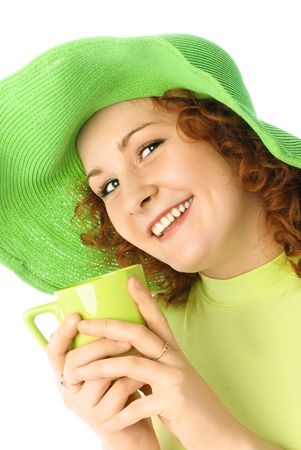 happy girl wearing a green summer hat drinking tea and smiling photo