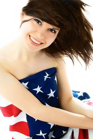 happy beautiful young brunette woman wrapped into an American flag photo