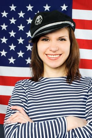 beautiful young confident sailor near the American flag photo