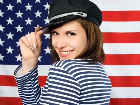 young beautiful coquettish sailor standing near the American flag and smiling photo