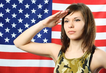 beautiful young woman standing opposite an American flag and wearing camouflage salutes photo