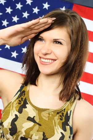 salutes: beautiful cheerful young woman dressed in camouflage salutes opposite an American flag Stock Photo