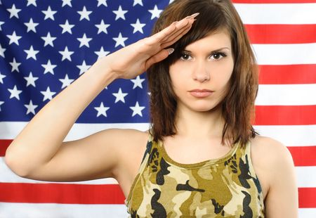 salutes: beautiful young woman dressed in camouflage stands near the American flag and salutes