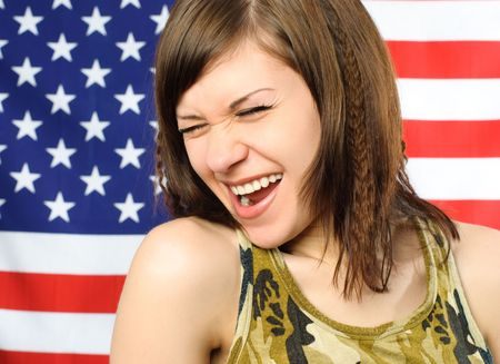 happy laughing young woman standing opposite an American flag photo