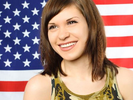 portrait of a happy smiling young woman standing near the American flag photo