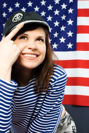 portrait of a cheerful young sailor standing opposite an American flag photo