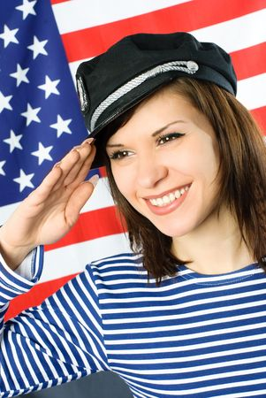 happy beautiful young sailor stands near the American flag and salutes photo
