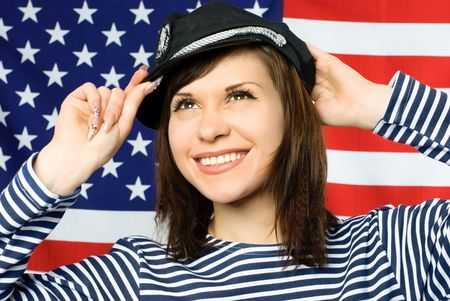 happy young beautiful sailor standing near the American flag photo