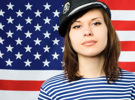 beautiful young confident sailor standing near the American flag photo
