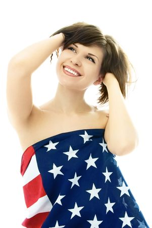 beautiful cheerful young nude woman wrapped into an American flag, isolated against white background photo