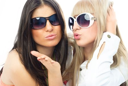 air kiss: two young glamorous friends wearing sun glasses and sending us an air kiss