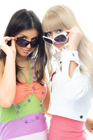 portrait of two beautiful young women trying on sun glasses photo