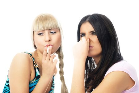 passive: portrait of two young women, one of them is going to smoke a cigarette and the other frowns and closes her nose Stock Photo