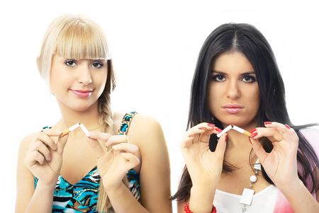 two young beautiful women breaking cigarettes and looking at us seriously photo