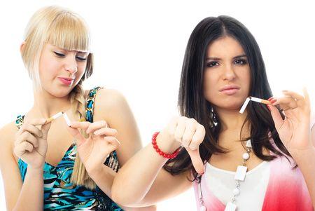 fille fumeuse: portrait de deux belles jeunes femmes de rupture de cigarettes et fronce les sourcils Banque d'images