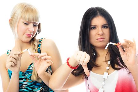 bad habits: portrait of two beautiful young women breaking cigarettes and frowning