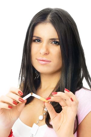 beautiful young brunette woman breaking a cigarette and looking at us seriously photo
