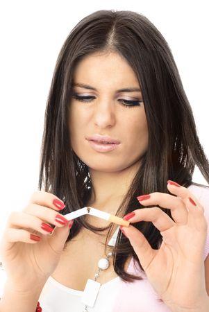 chica fumando: joven y bella mujer morena rompe un cigarrillo y ce�os fruncidos