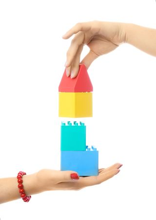 two people making a toy house, against white background photo